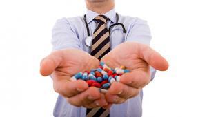 รูปคนแต่งตัวเป็นคุณหมอกำลังถือเม็ดยาอยู่ในมือแล้วยื่นออกมาให้