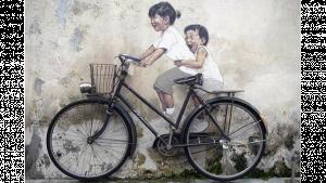 รูปประกอบเป็นรูปักรยานจอดข้างกำแพงที่มีรูปวาดเด็กอยู่สองคนอารมณ์เหมือนปั่นจักรยานคันนั้นอยู่