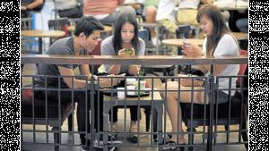 รูปคน 3 คนกำลังนั่งก้มหน้าใช้มือถือ
