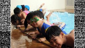 รูปประกอบเป็นเด็กหลายคนหัดว่ายน้ำ กำลังเกาะขอบสระและเอาขาตีน้ำ