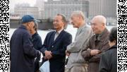รูปผู้สูงอายุยืนคุยกันริมแม่น้ำ
